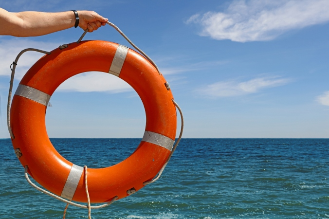 Man hand with lifebuoy ring over blue sea water
