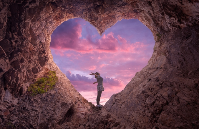 Young woman in heart shape cave towards the beautiful sky